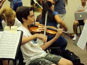 "As his audition approaches, Jay Coleman, seventh grade strings major, tunes his instrument. ""I was nervous, like most people were,"" Coleman said. ""I auditioned for two instruments, so by my second audition, I felt more comfortable."""