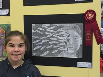 Sixth grader, Emma Kaminski displays her art piece.