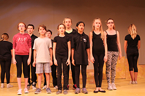 As the curtains rise, a group of sixth grade students perform a Greek theater piece. They earned critiques at school so that they could perfect their works at home.