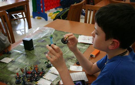 Fox Lopez, Geek Games member, plays HeroClix at the club meeting. HeroClix includes Superman mini action collectible figures and centers on the world of superheroes.