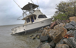A cabin cruiser that probably had broken loose from its moorings sits among the rocks Thursday, October 7, 2016  along the Banana River.  Hurricane Matthew a Category 4 storm brushed the Florida east coast. (Red Huber/Orlando Sentinel/TNS)