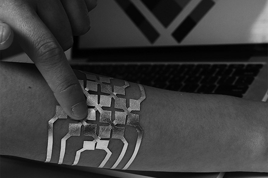 Controlling the computer with a finger, this DuoSkin tattoo is being used as a 2D trackpad. The process uses simple materials that involve vinyl film, thin tattoo paper, adhesive, and gold leaf sheets.