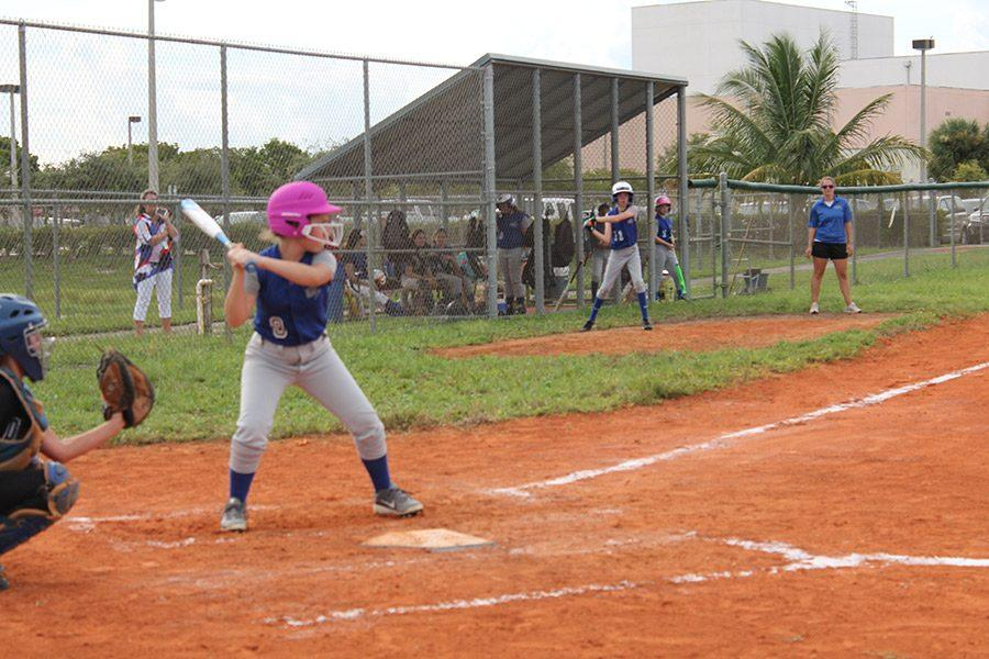 """Kaitlyn Riordan, seventh grade, third baseman gets in her stance to hit the ball. """"I chose to play softball because I thought it would be a good experience to make friends with people who like the same things as me,"""" Riordan said."""