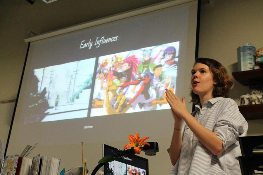 "Smiling, Rebecca Mock shows students her influences early in her career.  She gave students ideas on how to develop their own individual styles as artists, and how to work past any obstacles. ""She kept on telling us to keep trying. Even if you present work to someone who rejects it, eventually someone will take it,"" Sydney Williams, eighth grade visual major said."