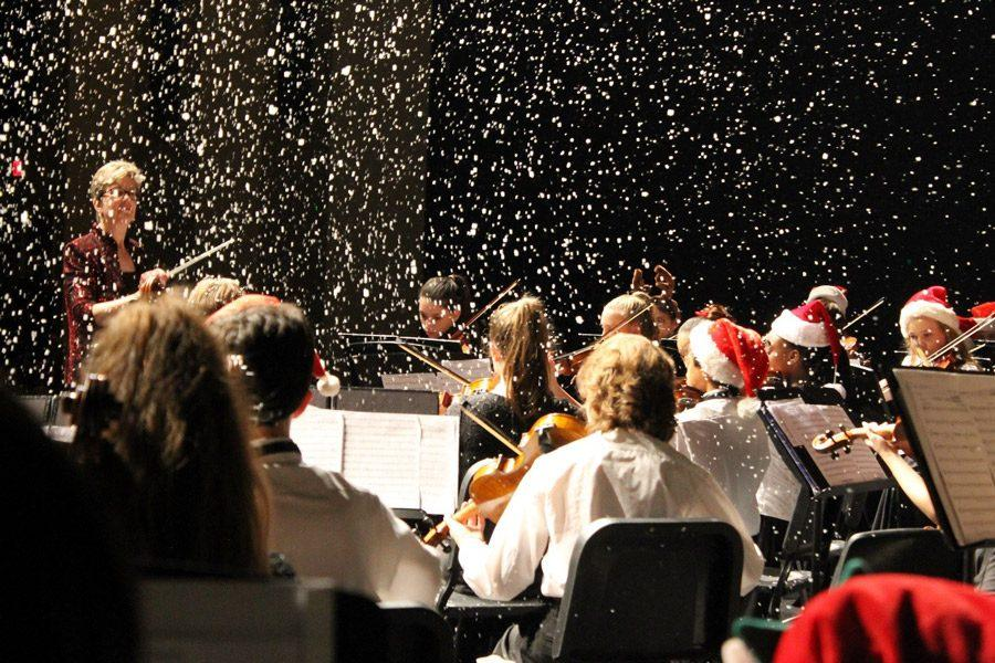 Strings Orchestra students perform as snow fills the theater. Volunteers prepared fake snow in machines that when turned on, it would turn soap into bubbles, to look like snow for a special effect.