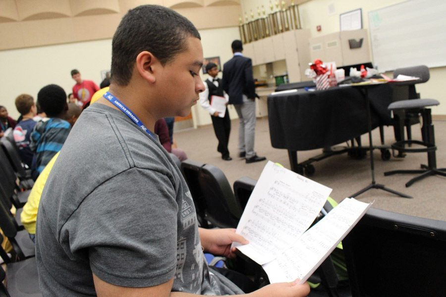 """Devin Cruz, eighth grade vocal major looks over and practices his songs. """"During a normal day of class, we usually cover our songs and we go over the order of the songs for our concert,"""" Cruz said."""