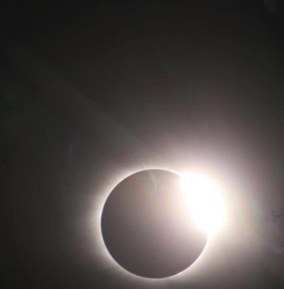 With eyes focusing on the eclipse, the moon slightly move, creating a diamond ring. A diamond ring effect, or the Bailey's Beads effect, was when the moon's craters allowed some sunlight to shine in through some places.