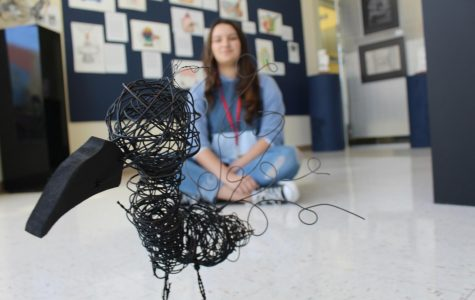 "With a watchful eye, Ariana Sanchez, seventh grade visual major, admires her sculpture in the Winter Showcase. The Winter Showcase was held in the Koch Gallery and students and were invited to view the artwork. ""We want to showcase our talent,"" Sanchez said. ""In a way, this is my performance."""